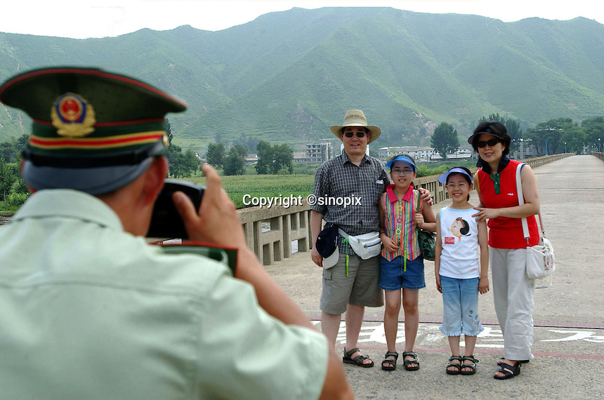 Surreal normality on the North Korean border as a People's Liberation Army border guard photographs a family of tourists at the Tumen Bridge border crossing where refugees are sent back to the North..01-AUG-02