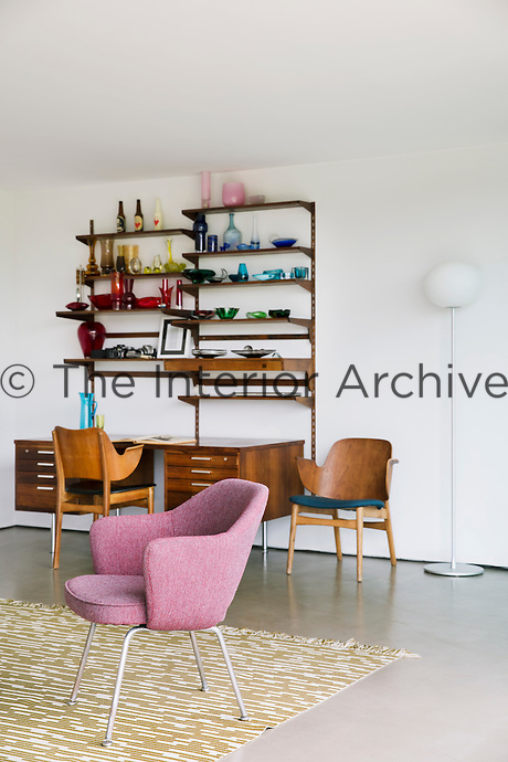 The sitting room is furnished in a minimalist style with a mixture of mid-century and contemporary pieces with a vintage Arne Jacobsen rug in the centre. The plywood armchairs are vintage pieces by Thonet and desk is Scandinavian mid-century.