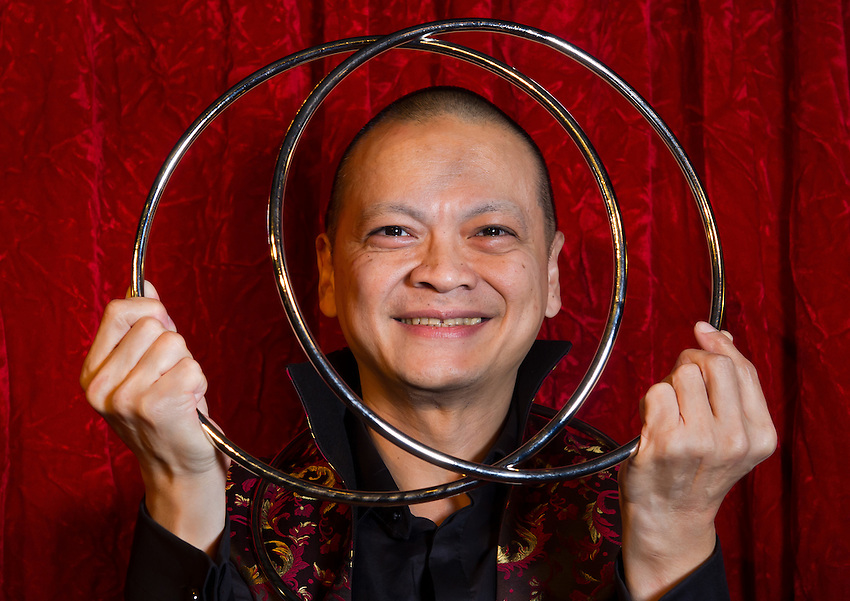 Quoc-Tien Tran performing with Chinese magic rings during a photo-shoot for publicity purposes at the Double Fond, café-théatre de la magie (café and magic theatre), at 1, place du Marché Ste Catherine, 75004 Paris.