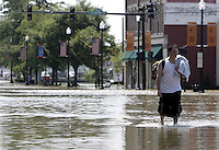 A Findlay resident walks down Main Street as flood waters from the Blanchard River start to recede after heavy rains caused flooding Thursday, August 23, 2007, in Findlay, Ohio. The Blanchard River was close to 7 feet above flood stage at Findlay yesterday morning, the highest since a 1913 flood.