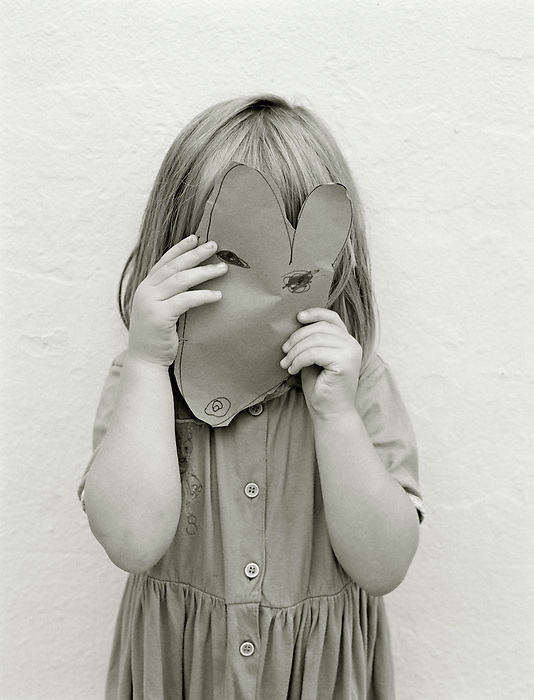 A three year old girl holds a home-made mask in front of her face, depicting a mouse.<br />