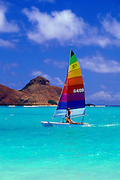 A catamaran with a vivid rainbow striped sail glides in front of the Moku lua islands off world famous Lanikai beach on the island of Oahu.
