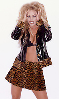 Photo of a blond glamour model making a growl. She's in a leopard print and vinyl mini skirt & jacket and a black lace bra.