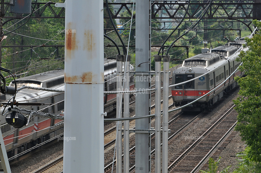 Metro-North Trains passing just West of the Railroad Station at Fairfield Metro Center. Electric Transmission Power towers in foreground. Connecticut Department of Transportation. Northeast Corridor, Serving Metro-North Commuter Railroad and Amtrak.