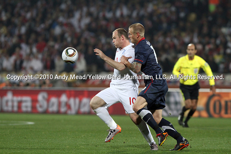12 JUN 2010:  Wayne Rooney (ENG)(10) tries to hold off Jay DeMerit (USA)(right) from the ball.  The England National Team played the United States National Team played to a 1-1 tie at Royal Bafokeng Stadium in Rustenburg, South Africa in a 2010 FIFA World Cup Group C match.