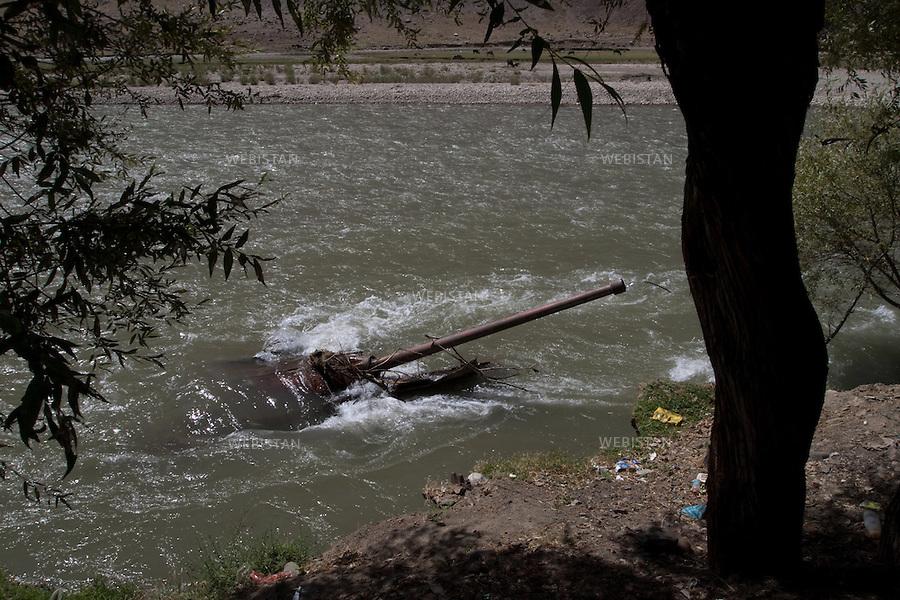 """AFGHANISTAN - VALLEE DU PANJSHIR - 18 aout 2009 : Riviere du Panjshir. Le canon d'une carcasse de char pris aux russes par les Moudjahidin du Commandant Massoud lors de leurs assauts pendant la guerre d'Afghanistan de 1979 - 1989 sort de l'eau. .La photographie appartient a la serie """"Il etait une fois l'Empire Russe"""". ..AFGHANISTAN - PANJSHIR VALLEY - August 18th, 2009 : Panjshir River. The canon of an abandoned Russian tank, seized by Commander Massoud's mujahideen during the Afghan war of 1979-1989, sticking out of the water..The photograph is part of the series """"Once Upon a Time, the Russian Empire."""""""