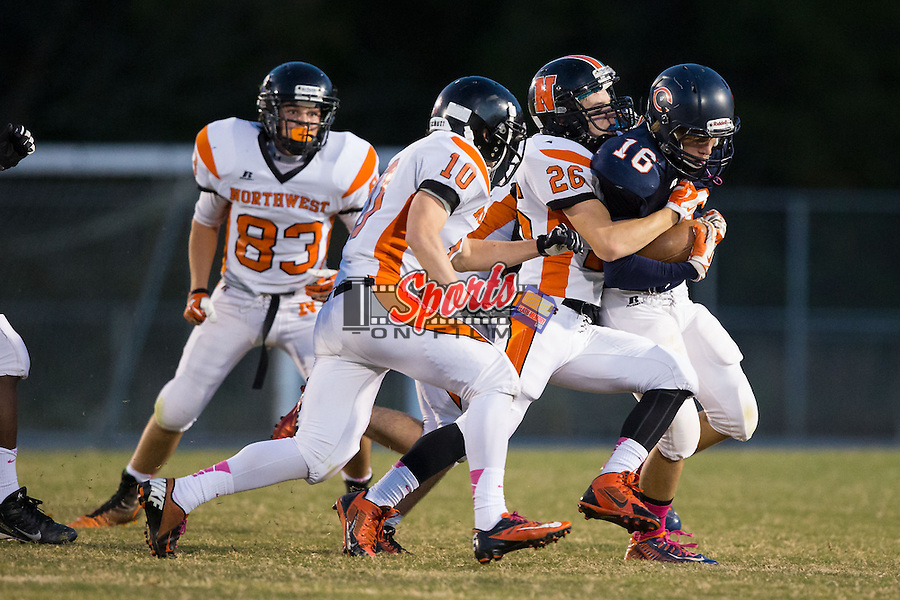 Cameron Rayfield (16) of the Carson Cougars is wrapped up by Clay Stewart (26) of the Northwest Cabarrus Trojans at Jesse Carson High School on October 24, 2014, in China Grove, North Carolina.  The Cougars defeated the Trojans 35-6.  (Brian Westerholt/Sports On Film)