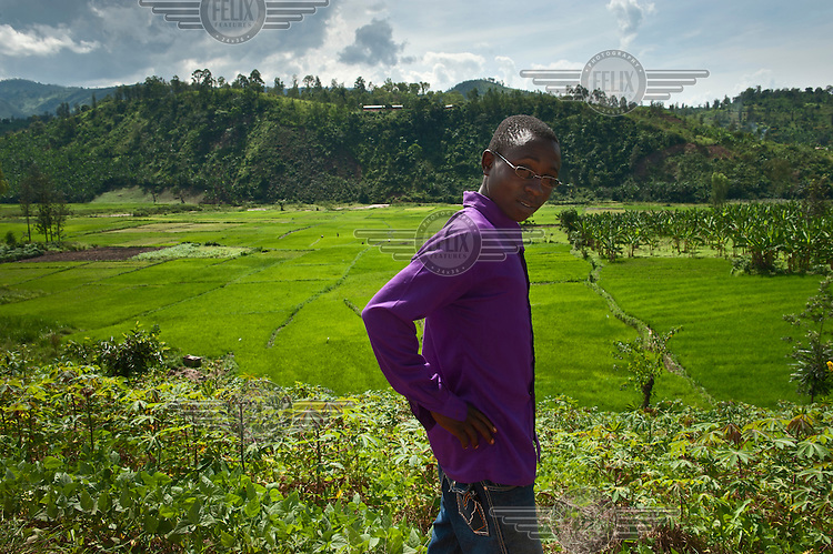 A young man stands in front of a valley of farmland where a variety of different crops are growing.