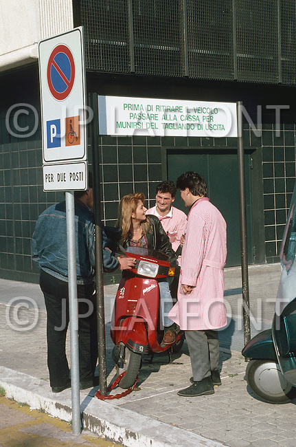 "April 27, 1990, Rome, Italy. Photographing for the book ""One day in the life of Italy"", this is an exploration of Rome. 8am, people are waiting for the bus, and some are using their bicycles or scooters."