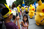 "A boy takes a picture of Pikachus during the parade at the ""1000 Pikachu Outbreak! at Yokohama Minatomirai"" on August 09, 2014. 1000 Pikachu performed at different areas of Minatomirai in Yokohama during the summer vacation event from August 9 to 17.  (Photo by Rodrigo Reyes Marin/AFLO)"