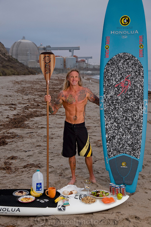 Ernie Johnson, a finish carpenter and paddle surfer, with his typical day's worth of food near the San Onofre Nuclear Generating Station in California. (From the book What I Eat: Around the World in 80 Diets.) The caloric value of his day's worth of food in the month of September was 3500 kcals. He is 45 years of age; 5 feet, 10 inches tall; and 165 pounds. MODEL RELEASED.