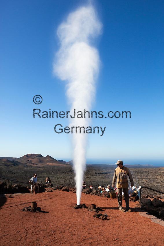 Spain, Canary Island, Lanzarote, near Yaiza: Parque Nacional de Timanfaya (Timanfaya National Park) - Islote de Hilario - demonstration of water instantly turning to steam by volcanic subterranean heat |Spanien, Kanarische Inseln, Lanzarote, bei Yaiza: Islote de Hilario im Timanfaya Nationalpark (Parque Nacional de Timanfaya), um die unterirdische, vulkanische Hitze zu demonstrieren schuettet ein Parkranger in ein in den Boden fuehrende Rohr einen Eimer Wasser, das sofort als Wasserdampf aus dem Rohr nach oben schiesst