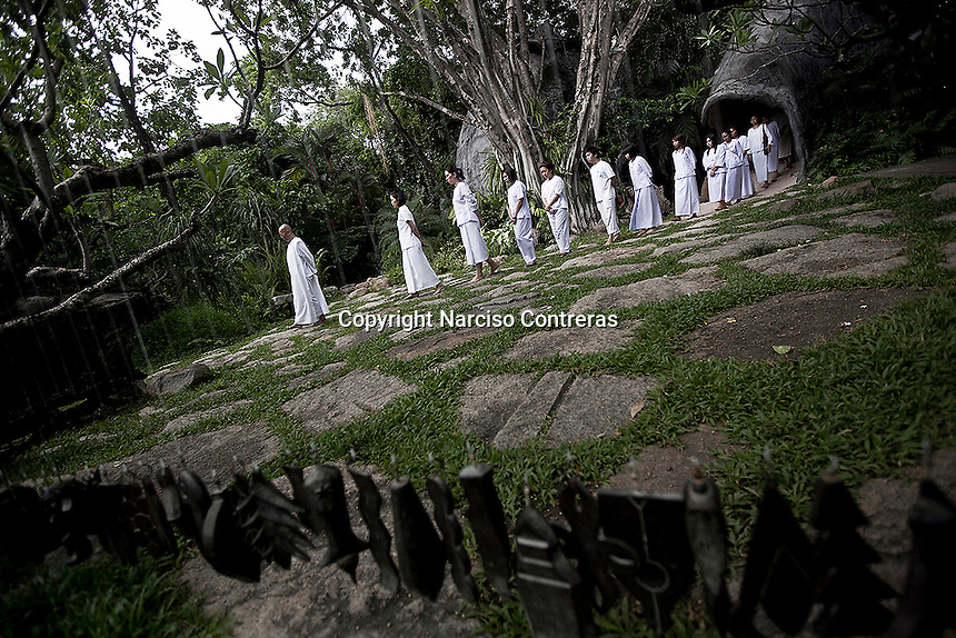 """MAE CHEE KON KHAI leads a walking meditation to a female group as part of the Sathira Dhammasathan spiritual teaching program for the lay people. Vanished by centuries the lineage of """"Bhikkhu?nii"""" (Order of Nuns) has been brought to the ongoing Thai society's debate. White-clad thai nuns, who keep the eight precepts and have their heads and eyebrows shaved are known as the lon-existing """"mae chees"""" (low category to call the lay nuns). Females who have turned to religous life, as renunciants, live ostracized and marginalized by the Sangha (Buddhist community) and Thai society, denying them full access to the monastic life as well as rights and support from the government. Today nunhood is not recognized by any asian country belong to the Theravada Buddhist order. Most of the eight precept holders live in temples run by male abbots, at the shadow of the monks; with the exceptional existence of a few para-monastic institutions as the Sathira Dhammasathan meditation centre, where """"mae chees"""" are not allow to held a temple, but not denied to practice the spiritual life."""