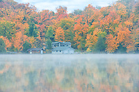 Fog on Horseshoe Lake in autumn with cottage , Near Parry Sound, Ontario, Canada