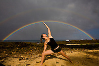 Young woman practicing yoga pose at Shark's Cove on the North Shore of Oahu, with double rainbow in the background