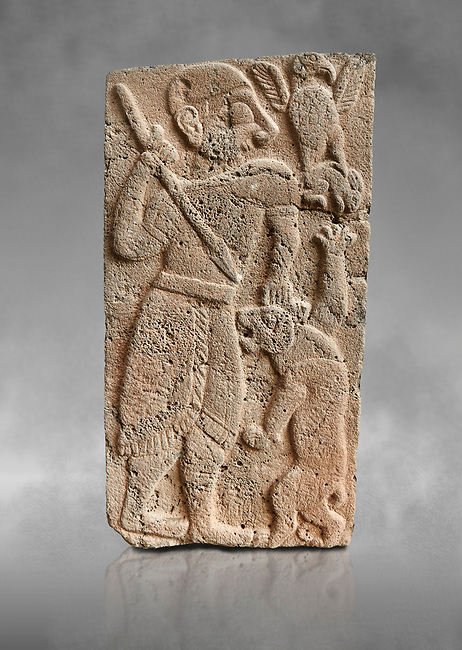 Pictures & images of the North Gate Hittite sculpture stele depicting Hittite God hunting a lion. 8th century BC. Karatepe Aslantas Open-Air Museum (Karatepe-Aslantaş Açık Hava Müzesi), Osmaniye Province, Turkey. Against grey art background