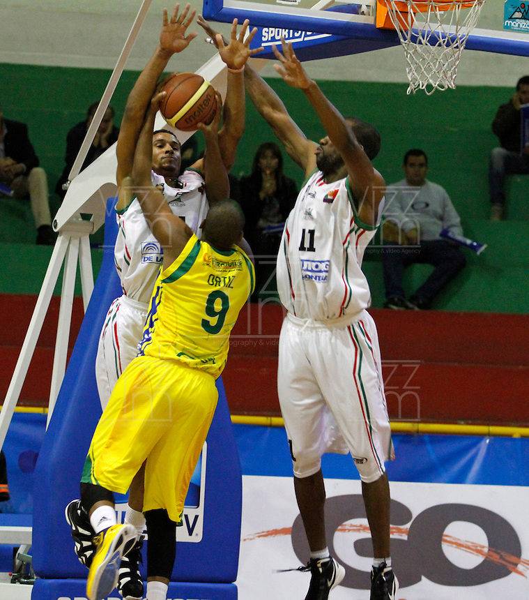 MANIZALEZ -COLOMBIA-27-05-2013. Justin Garris (I) y Cesar Cortés (D) de Once Caldas disputa el balón con  Stalin Ortiz (C) de Bambuqeros durante partido de los PlayOffs de la  Liga DirecTV de baloncesto Profesional de Colombia realizado en el coliseo Municipal de Caldas./  Justin Garris (L) and Cesar Cortés (R) of Once Caldas fights for the ball with Bambuqueros player Stalin Ortiz (C) during match of PlayOffs of  DirecTV professional basketball League in Colombia at Caldas Municipal coliseum in Manizales. Photo: VizzorImage/Yonboni/STR