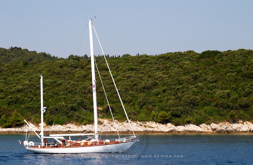 A two mast white sailing boat sailing on the deep blue sea water between Korcula and Peljesac. Korcula Island. Korcula Island. Peljesac peninsula. Dalmatian Coast, Croatia, Europe.