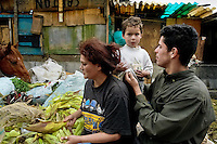 Colombian family members peel off fresh corn in the 'Invasión', a temporary slum in Bogota, Colombia, 1 April 2006. The internal armed conflict in Colombia together with lack of social network caused appearence of small invasion slums in all Colombian urban zones in last years. These illegal settlements rise quickly in free uncontrolled spaces between industrial buildings, both in the city centres and peripheries. Shacks do not have sanitation network, neither electricity. Most of their inhabitants are war fugitives violently displaced from their original lands in the country by guerrilla or paramilitary forces. Picking up the rubbish and recycling it is a common survive strategy for people living in these temporal ghettos until those are not dismantled by city administration.