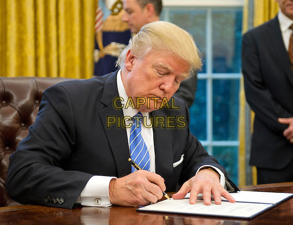 United States President Donald Trump signs the last of three Executive Orders in the Oval Office of the White House in Washington, DC on Monday, January 23, 2017.  These concerned the withdrawal of the United States from the Trans-Pacific Partnership (TPP), a US Government hiring freeze for all departments but the military, and &quot;Mexico City&quot; which bans federal funding of abortions overseas.<br /> CAP/MPI/CNP/RS<br /> &copy;RS/CNP/MPI/Capital Pictures