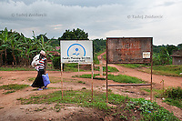 Woman with child walks to Bbanda Health Center, Mityana district, Uganda. In addition to government health centers there are also private health centers that many people attend since they prefer them over government health centers.