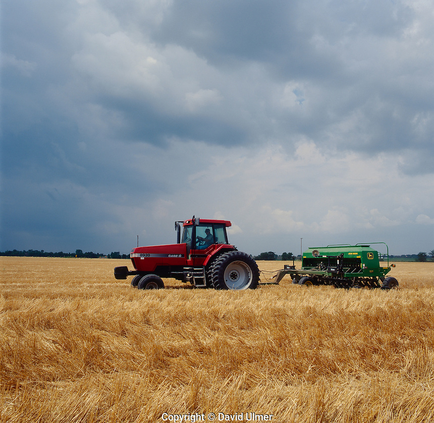 Case IH 8929 tractor pulling a John Deere no-till drill through fresh winter wheat stubble under threatening skies.