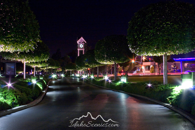 Looking out of the lighted, tree lined drive into the Coeur D Alene Resort, towards the clock tower in downtown Coeur D Alene, Idaho, USA