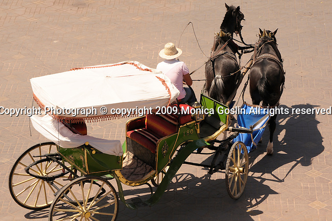 A green carriage in the Place Djemaa El-Fna  in Marrakesh, Morocco.