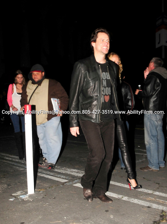 .December 21st 2011 ..Jim Carrey holding hands with mystery woman leaving the Guns N Roses concert in Los Angeles. Jim was wearing an upside down I love Rock N Roll t shirt..AbilityFilms@yahoo.com.805-427-3519.www.AbilityFilms.com.