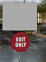 Exit Only Sign of reflective doorway with blank sign panel over.