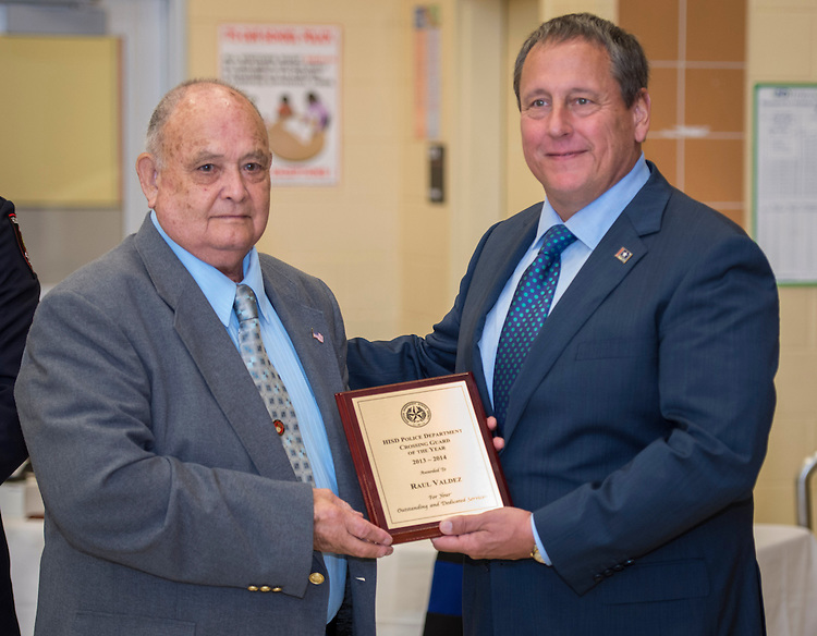 Raul Valdez, left, receives the Crossing Guard of the Year award from Chief Robert Mock, right, during the Houston ISD Police awards banquet at Thompson Elementary School, August 15, 2014.