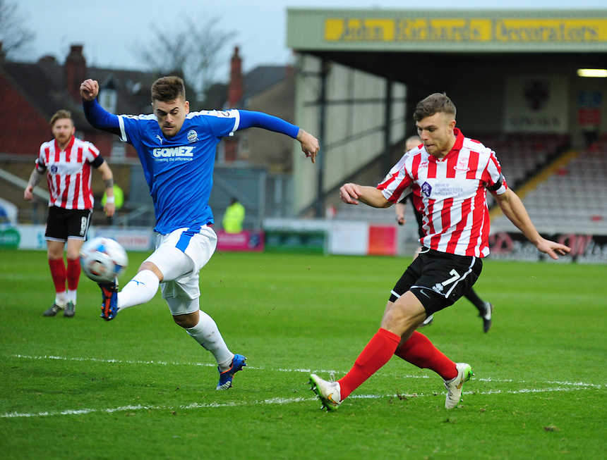 Lincoln City's Jack Muldoon gets a cross in under pressure from Dover Athletic's Sam Magri<br /> <br /> Photographer Andrew Vaughan/CameraSport<br /> <br /> Football - Vanarama National League - Lincoln City v Dover Athletic - Saturday 9th January 2016 - Sincil Bank - Lincoln<br /> <br /> &copy; CameraSport - 43 Linden Ave. Countesthorpe. Leicester. England. LE8 5PG - Tel: +44 (0) 116 277 4147 - admin@camerasport.com - www.camerasport.com
