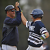 Mike Reda #20, St. Dominic designated hitter, right, gets congratulated by first base coach Angelo Coscia after breaking a scoreless tie with an run-scoring single in the bottom of the fifth inning of a CHSAA varsity baseball game against Holy Trinity at Charles Wang Athletic Complex in Muttontown on Friday, Apr. 22, 2016. St. Dominic won by a score of 4-0.