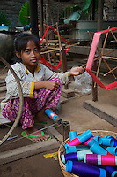 A young girl weaving in the village on Silk Island outside Phnom Penh, Cambodia. Traditional Khmer Silk production