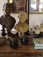 A collection of antique busts is displayed on a polished tabletop together with books, found objects and contemporary abstract pieces