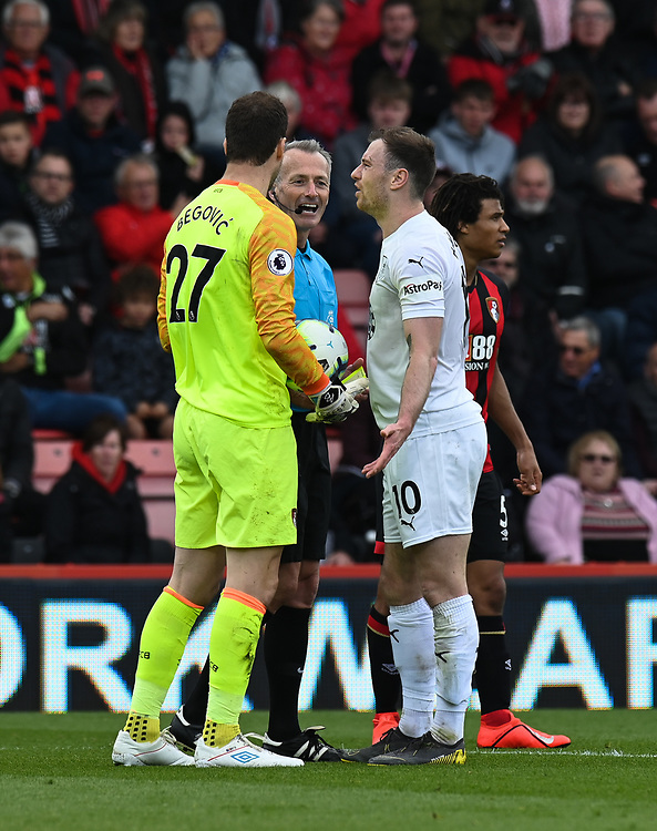 Burnley's Ashley Barnes (right) and Bournemouth's Asmir Begovic (left) with referee Martin Atkinson after getting a yellow card <br /> <br /> Photographer David Horton/CameraSport<br /> <br /> The Premier League - Bournemouth v Burnley - Saturday 6th April 2019 - Vitality Stadium - Bournemouth<br /> <br /> World Copyright © 2019 CameraSport. All rights reserved. 43 Linden Ave. Countesthorpe. Leicester. England. LE8 5PG - Tel: +44 (0) 116 277 4147 - admin@camerasport.com - www.camerasport.com
