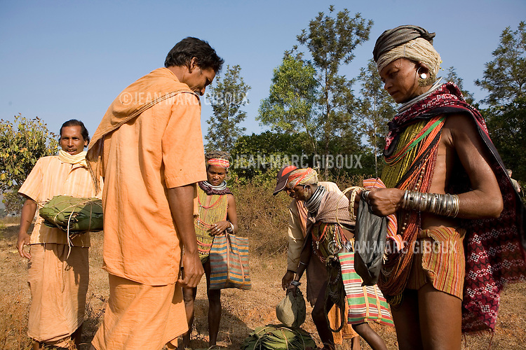 """FEBRUARY 12 & 13, 2009 : BONDA WOMEN SELL THEIR FOREST HARVEST TO TRADERS ON THE WAY TO THE MARKET IN ONUKUDELI.  BONDAS, GADABAS , TRIBALS COME FROM THE HILLS FOR THE THURSDAY MARKET IN ONUKUDELLI, SOUTH OF JEYPORE IN WESTERN ORISSA. THIS IS PART OF INDIA'S TRIBAL BELT. THE BONDA  OR BONDO ARE AN ANCIENT TRIBE OF PEOPLE NUMBERING APPROX 5000 WHO LIVE IN THE ISOLATED HILL REGION OF SOUTHWEST ORISSA, THE BONDA ARE A SCHEDULED TRIBE IN INDIA AND ARE ALSO KNOWN AS REMO (MEANING """"PEOPLE"""" IN BONDA LANGUAGE). THE TRIBE IS THE OLDEST AND MOST PRIMITIVE IN MAINLAND INDIA AND THEIR CULTURE HAS LITTLE CHANGED IN OVER THOUSAND YEARS. THEIR ISOLATION AND AGGRESSION PRESERVED THEIR CULTURE DESPITE THE PRESSURE OF AN EXPENDING INDIAN POPULATION. WOMEN WEAR THICK SILVER NECKLACE BANDS AND LONG COLORFUL NECKLACES MADE OF BEADS."""