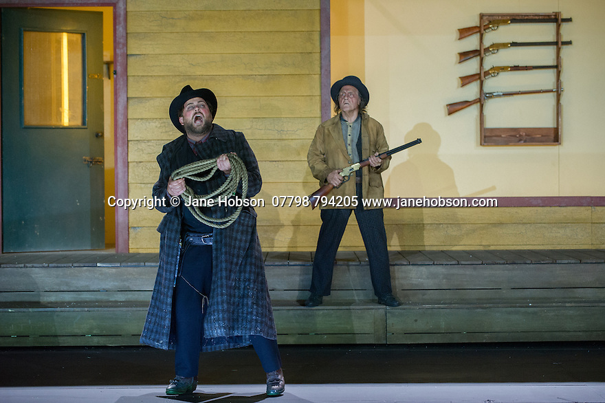 "London, UK. 30.09.2014. English National Opera's production of ""The Girl of the Golden West"", by Giacomo Puccini, directed by Richard Jones, conducted by Keri-Lynn Wilson, opens at London Coliseum. Picture shows: Craig Colclough (Jack Rance) and Graham Clark (Nick). Photograph © Jane Hobson."