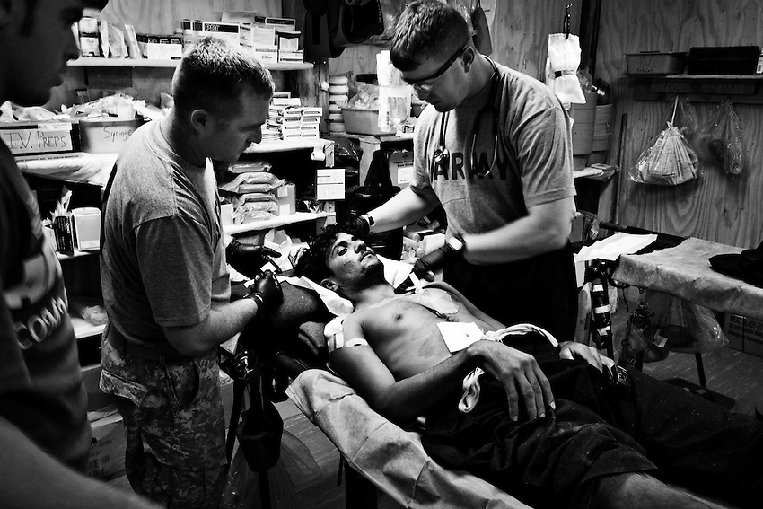 Sgt. Anthony Blake (R) and Corporal Kenith Nichols (L) treat an Afghan construction worker wounded by a grenade in an attack by the Taliban in the Pesh Valley near the village of Kandigal, COP Michigan, Kunar Province, Afghanistan, Sunday, Sept 27, 2009. The wounded man is a member of a construction team working on the main road through the Pesh Valley.
