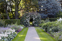 A cobbled path leads between formal flowerbeds towards an arbour covered in white roses