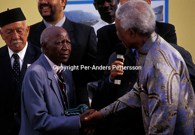 "CAPE TOWN, SOUTH AFRICA - FEBRUARY 11: Dan Ndzabela, age 82, (L) with former president Nelson Mandela on February 11, 2004 in Cape Town, South Africa. Dan Ndzabela was one of the first to be forced out of District Six, a lively area in Cape Town, that was declared ""white only"" during Apartheid. Dan was forced to move in 1959 to a grim township outside Cape Town and he always wanted to return. On February 11, this year, he was given a key from former President Nelson Mandela at a ceremony celebrating the first finished houses and the start of the return for residents forced away many years ago. .(Photo: Per-Anders Pettersson/ iAfrika Photos......."