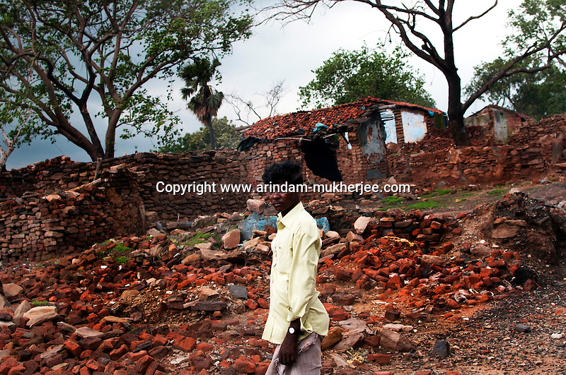 A man standing in front of his destroyed house at Ghannudi, one of the most affected area due to mine fire. A huge coal mine fire is engulfing the city of Jharia from all its sides. All scientific efforts have gone in vain to stop this raging fire. This fire is affecting lives of people living in and around Jharia. Jharkhand, India. Arindam Mukherjee.