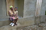 Christiana Herard, 69, talks with her 6-year old granddaughter Chisland on the porch of her new home in Djondgon, a village near Jean-Rabel in northwestern Haiti. The family's previous house was destroyed during Hurricane Matthew in 2016, and Church World Service, a member of the ACT Alliance, helped the family build their sturdy new home.