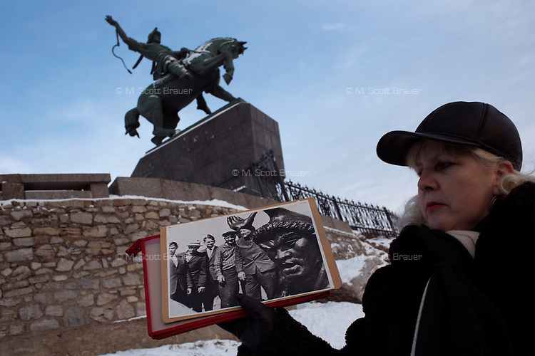 A tour guide stands in front of a monument to Bashkir national hero Salavat Yulayev stands above Ufa, Bashkortostan, Russia.