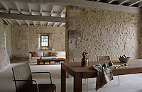Contemporary meets antique in this living space with the sleek modern furniture contrasting with the old stone walls