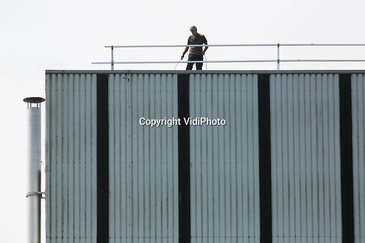 Foto: VidiPhoto<br /> <br /> DODEWAARD - Bedrijvigheid op het dak van de voormalige kerncentrale in Dodewaard dinsdag. Om te voorkomen dat er radioactieve straling naar buiten lekt of regenwater naar binnen komt en besmet raakt, wordt jaarlijks onderhoud gepleegd en inspecties gehouden aan en in het gebouw. Dinsdag is het dak van het reactorgebouw aan de beurt. De voormalige centrale wordt pas in 2045 ontmanteld als de straling zodanig is vervallen dat sloop veilig kan plaatsvinden. Binnen de muren bevindt zich nog radioactief materiaal, waaronder het reactorvat. Tot 2045 wordt het grotendeels dichtgemetselde gebouw ook nog bewaakt en vallen alle werkzaamheden onder verleende vergunningen. De onderhoudswerkzaamheden op het dak worden uitgevoerd door installatiebedrijf Spiek &amp; De Vries uit Andelst.