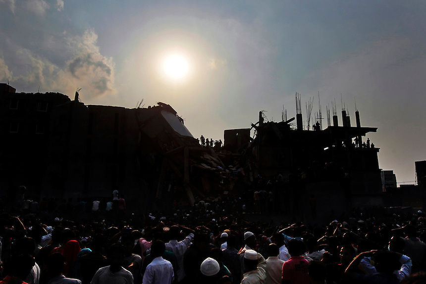 Rescue workers and people look for survivors after an eight-story building housing several garment factories collapsed in Savar, near Dhaka, Bangladesh, Wednesday, April 24, 2013.