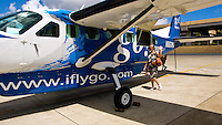 Tourist passenger at Honolulu Int'l airport boarding go! airlines prop plane to Molokai