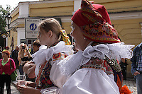 Women dressed in the traditional Moravian costume at The ride of Kings in Prague, Europe May 2015.<br /> <br /> Twelve-year-old Frantisek Libosvar dressed as a girl and with a rose in his mouth leads the royal procession during Ride of the Kings as part of Navalis Celebrations on May 15, 2015 in Prague, Czech Republic. The Navalis Saint John's celebrations take place to commemorate Czech saint and Prague native, Saint John of Nepomuk, patron of all people of the water. <br /> <br /> <br /> The Ride of the Kings takes place during the spring, as a part of the Pentecost traditions . A group of young men ride through a Prague in a ceremonial procession. The ride is headed by chanters, followed by pageboys with unsheathed sabres who guard the King &ndash; a young boy with his face partially covered, holding a rose in his mouth &ndash; and the rest of the royal cavalcade. The King and pageboys are dressed in women&rsquo;s ceremonial costumes, while the other riders are dressed as men. The entourage rides on decorated horses, stopping to chant short rhymes that comment humorously on the character and conduct of spectators. The chanters receive donations for their performance, placed either in a money box or directly into the riders&rsquo; boots. The King&rsquo;s retinue returns home after a few hours of riding, and celebrates in the evening at the house of the King with a small feast, music and dancing. The practices and responsibilities of the Ride of the Kings are transmitted from generation to generation. The traditional paper decorations for the horses and the ceremonial costumes, in particular, are made by women and girls familiar with the processes, colour patterns and shapes specific to each village.