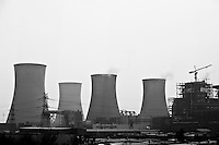 Daytime landscape view from the Tianjin Binhai Light Rail of cooling towers and smokestacks at an industrial site near the Binhai New Area Tanggu District in Tiānjīn.  © LAN